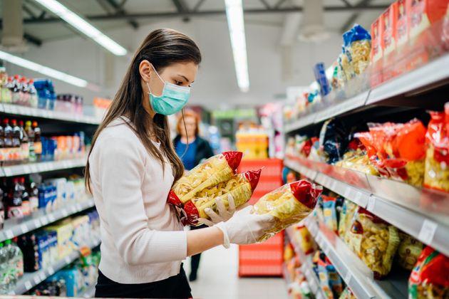 Una mujer elige un paquete de pasta en el
