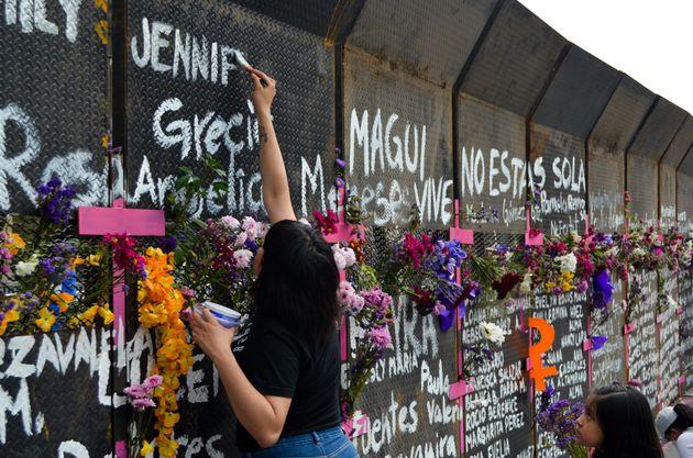Una mujer y su hija pintan nombres en el muro de paz, en Ciudad de