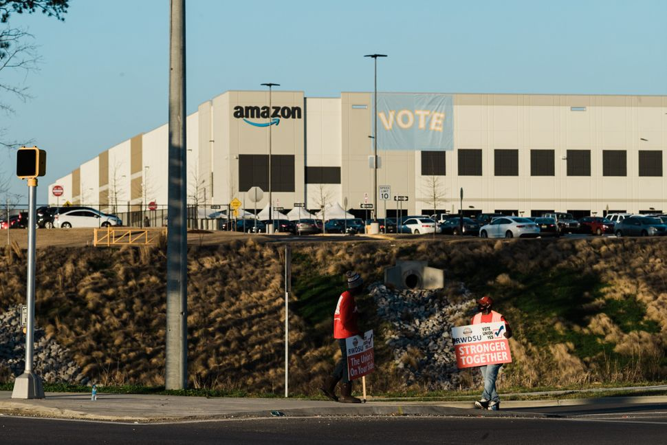 Union organizers from the Retail, Wholesale, and Department Store Union rally support as workers change shifts outside Amazon