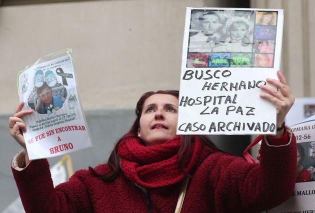 Una mujer muestra carteles con su historia, en una protesta en Madrid sobre casos de bebés