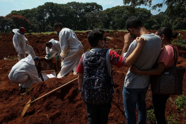 SAO PAULO, BRAZIL - MARCH 12: Relatives mourn as cemetery workers bury a victim of coronavirus (COVID-19)...