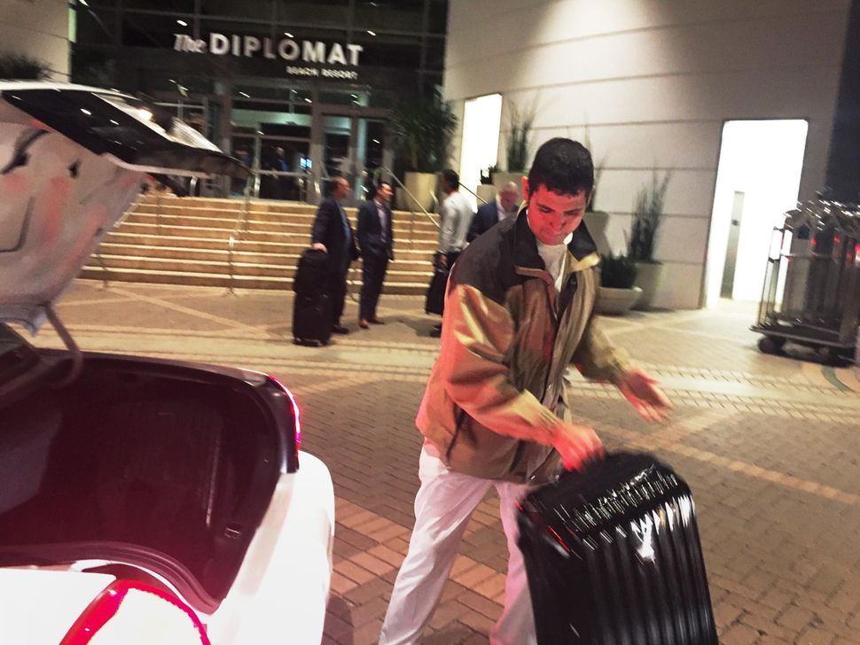 Julio Lopez handles a suitcase at the Diplomat Beach Resort in Hollywood, Florida, before COVID-19 forced it to close. The 16