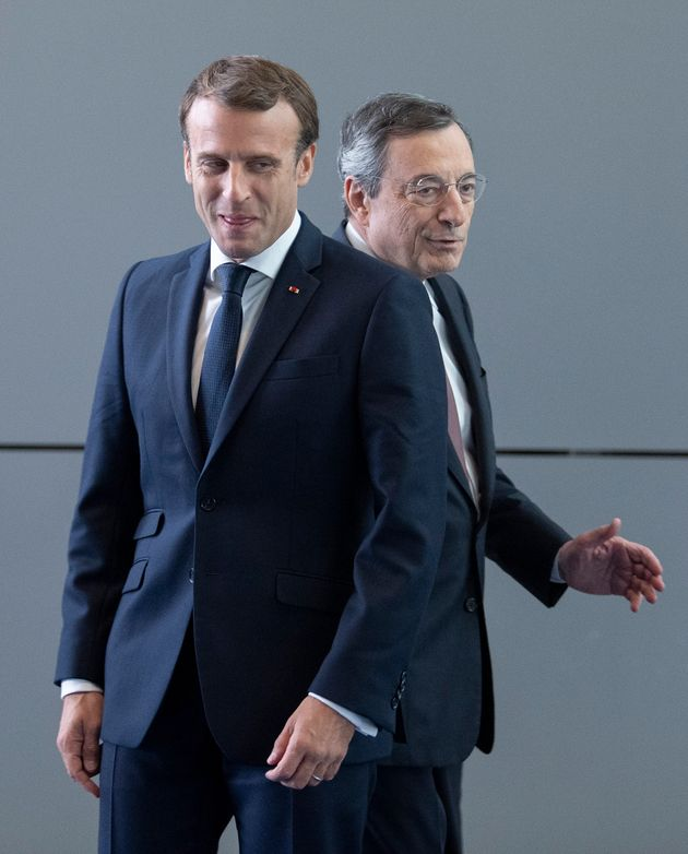 Mario Draghi (R), outgoing President of the European Central Bank (ECB) walks behind French President...