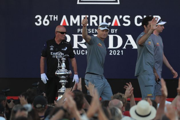 Luna Rossa Prada crew members walk past the America's Cup, affectionately known as the Auld Mug, after...