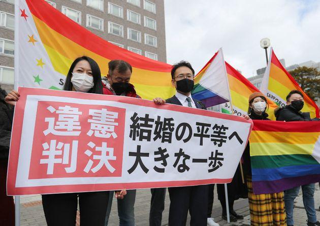 Des militants brandissent le drapeau arc-en-ciel devant la cour de justice de Sapporo (Hokkaido), ce...