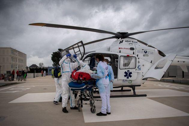 Du personnel médical transporte via un hélicoptère médical un patient évacué...