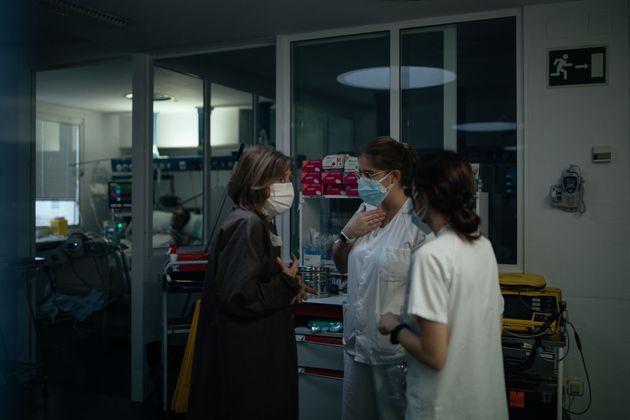 Un mujer conversa con dos sanitarias en el