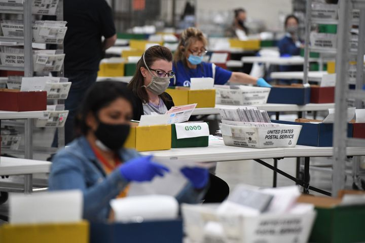 Election workers extract mail-in ballots from their envelopes and examine the ballot for irregularities at the Los Angeles Co