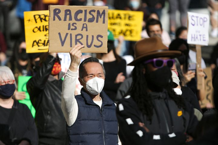 "A man holds a sign that reads ""Racism is a Virus"" during the ""We Are Not Silent"" rally against anti-Asian hate in response to"
