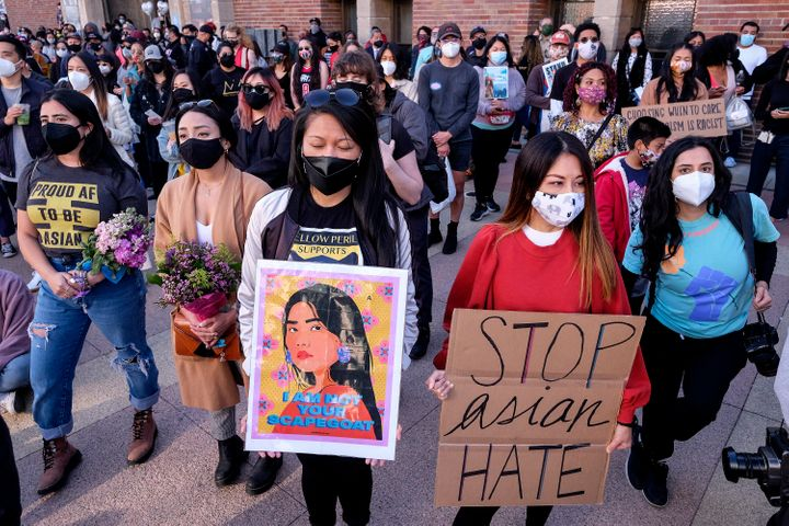"Demonstrators wearing face masks and holding signs take part in a rally ""Love Our Communities: Build Collective Power"" to rai"