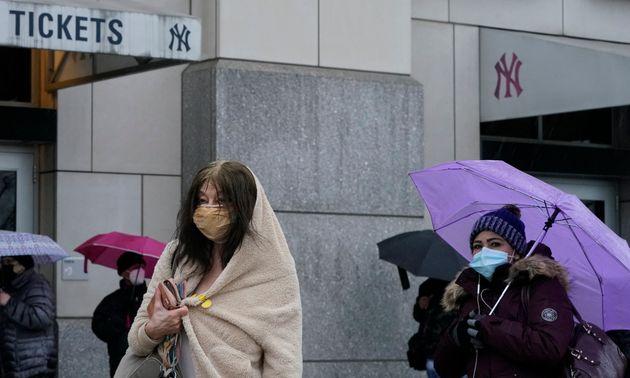 Des patients font la queue sous la pluie devant le Yankee Stadium à New York pour se faire vacciner contre...