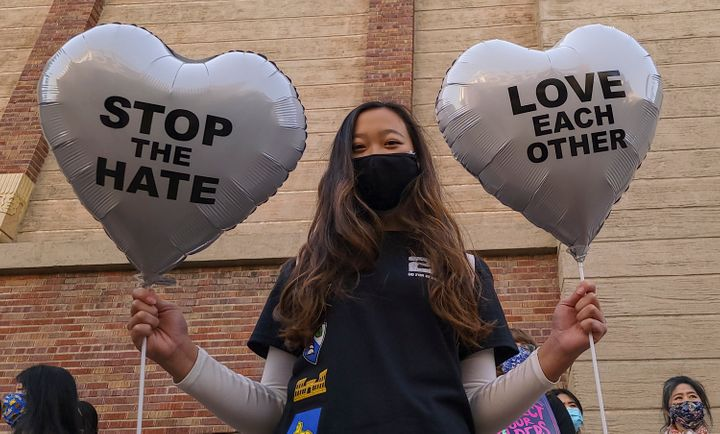 In this March 13, 2021, file photo, Chinese-Japanese American student Kara Chu, 18, holds a pair of heart balloons decorated