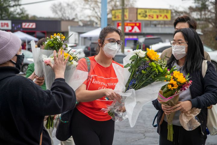 In this March 17, 2021, file photo, Roula AbiSamra, center, and Chelsey, right, prepare to lay flowers bouquets at a makeshif