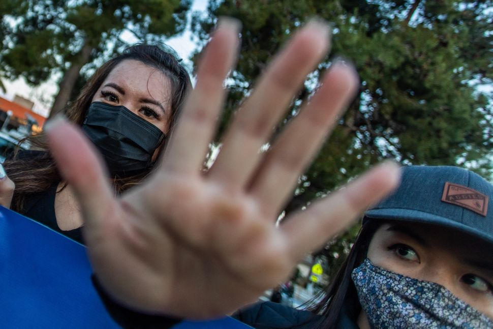 Clover and Julie Tran stand with outstretched hands during a candlelight vigil in Garden Grove, California, on March 17, 2021