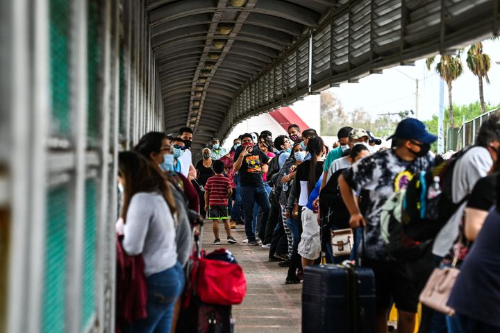 Migrants mostly form Central America wait in line to cross the border at the Gateway International Bridge into the US from Ma