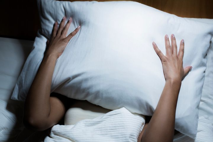 Woman in bed, covering her face with pillow