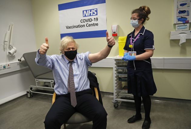 Boris Johnson gives thumbs up after receiving the first dose of AstraZeneca vaccine administered by nurse...