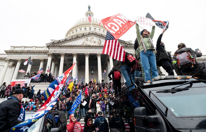 Supporters of Donald Trump stand on a U.S. Capitol Police armored vehicle as others take over the steps of the Capitol on Jan