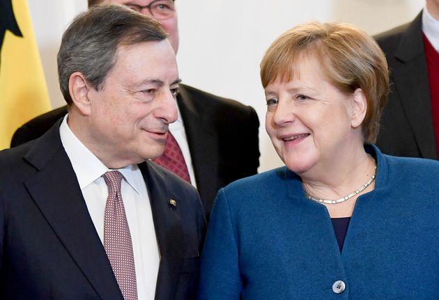 31 January 2020, Berlin: Former ECB President Mario Draghi talks to Chancellor Angela Merkel (CDU) at...
