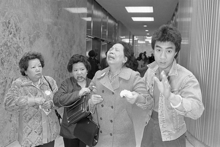 A relative, left, helps Lily Chin (center) leave Detroit's City-County Building after two white autoworkers beat her son, Vin