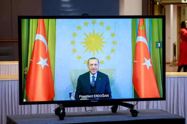 Turkey's President Recep Tayyip Erdogan is seen on a screen during a video call with European Commission...