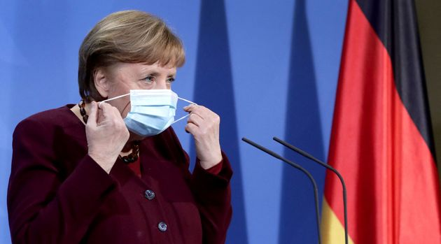 German Chancellor Angela Merkel takes her face mask off as she arrives to a press conference at the chancellery...