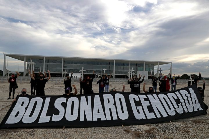 "Demonstrators hold crosses to represent people who have died of COVID-19 behind the Portuguese phrase ""Bolsonaro genocide"" as"