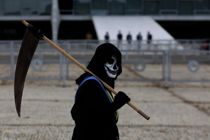 A demonstrator dressed as death and wearing a mock presidential sash walks outside Planalto presidential palace during a prot