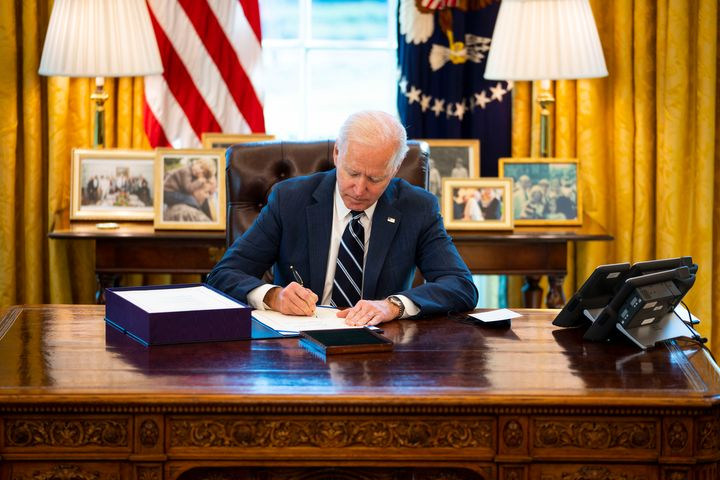 President Joe Biden signs the American Rescue Act bill into law in the Oval Office of the White House on March 11 in Washingt