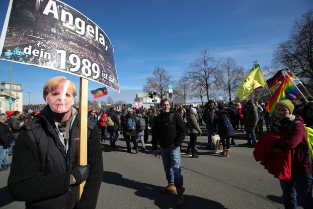 A protestor wearing a mask with an image of German Chancellor Angela Merkel holds up a placard with the...