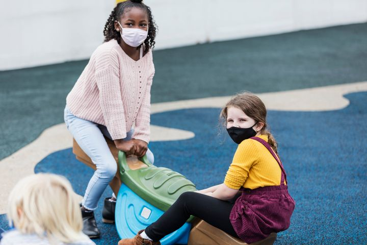Two 7-year-old girls playing on a seesaw, wearing protective face masks during the COVID-19 pandemic.
