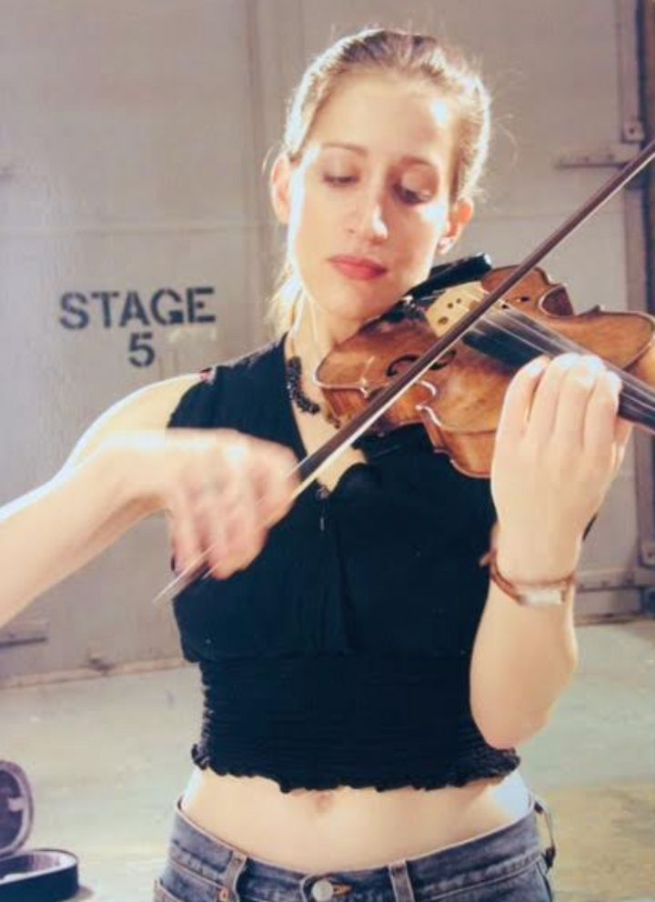 The author practices her violin at Silvercup Studios in New York City during a break in filming