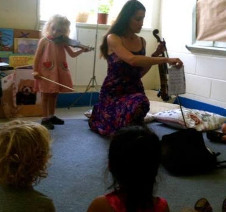 The author and one of her daughters teach violin lessons.