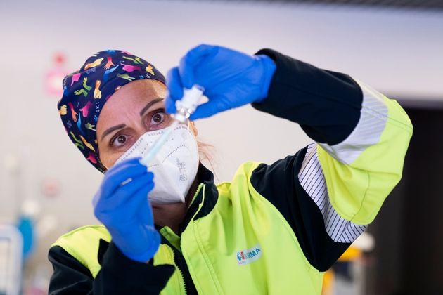 Una sanitaria prepara una dosis de la vacuna de AstraZeneca en el estadio Wanda Metropolitano de