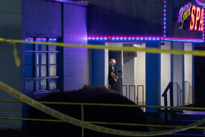 A police officer stands outside a massage parlor where three people were shot and killed on March 16, 2021, in Atlanta. The s