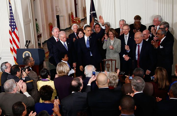 President Barack Obama is applauded after signing the Affordable Care Act during a ceremony with fellow Democrats in the East