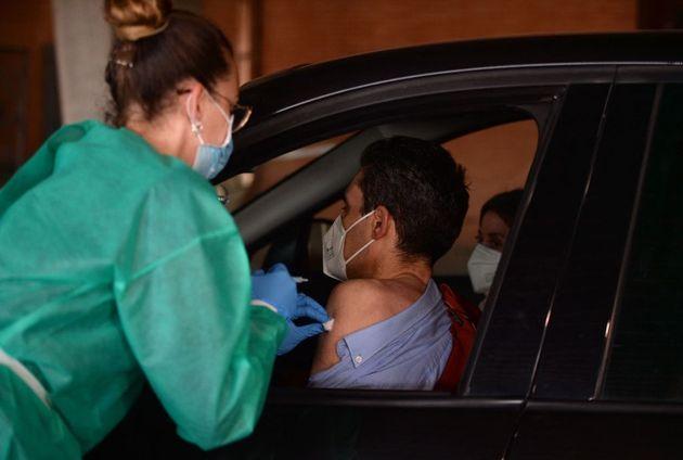 Una sanitaria administra una vacuna a los ocupantes de un coche en