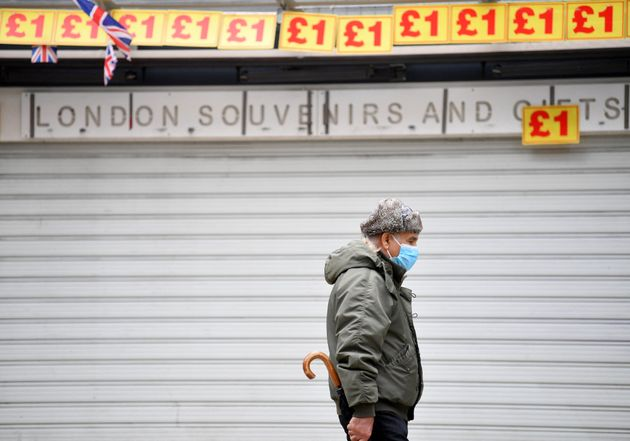A pedestrian wearing a face covering walks past a souvenir shop, closed due to Covid-19, in central London...