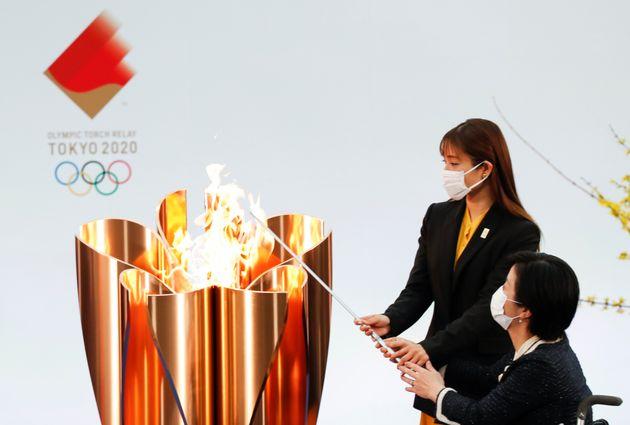 La actriz Satomi Ishihara y al atleta paralímpico Aki Taguchi, encendiendo el pebetero olímpico...
