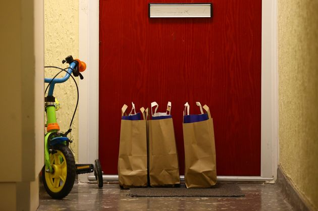 Bags containing meals for school children on the doorstep of an apartment in a block of flats in