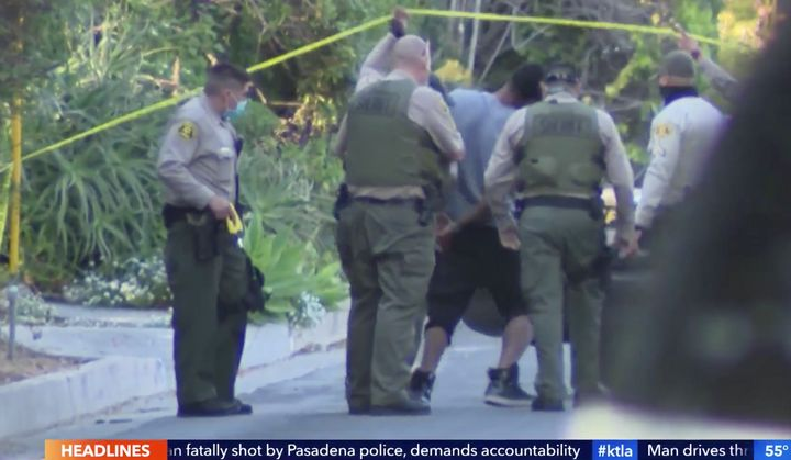 Robert Cotton is seen being taken into custody outside of a Los Angeles County house where authorities said two people were f