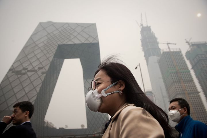 A woman wears a protective pollution mask on a street in Beijing, March 20, 2017.