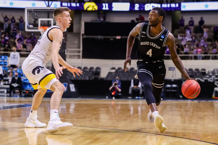 Oscar Frayer, right, dribbles up the court in a first-round NCAA Tournament game against Iowa.