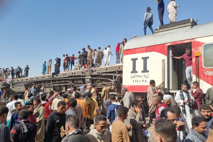 26 March 2021, Egypt, Tahta: People gather to inspect damaged train cars after two passenger trains collided near Tahta in So