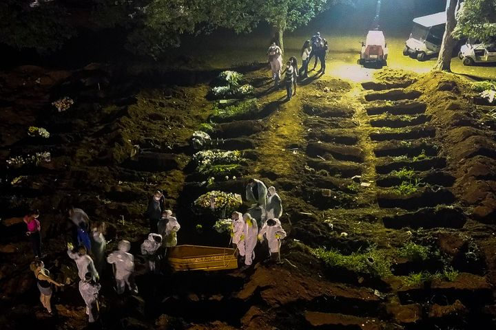 Cemetery workers carry a coffin during the first burial at night during the coronavirus pandemic at the Vila Formosa Cemetery