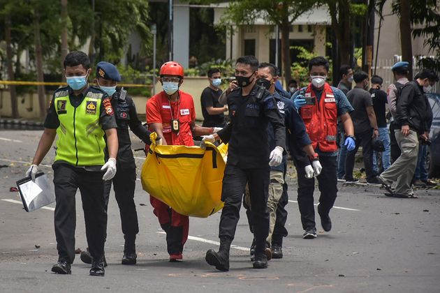 Indonesian police carry a bag with the remains of a suspected suicide bomber after an explosion outside...