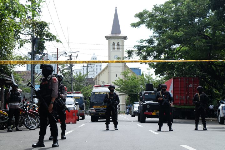 MAKASSAR, INDONESIA - MARCH 28: Police officers stand guard in the front of the Sacred Heart of Jesus Cathedral after a suici