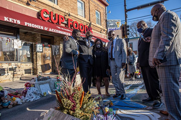 George Floyd's family, including brother Philonise Floyd (2nd L), and Floyd family lawyer Ben Crump (R) visit a memorial on M