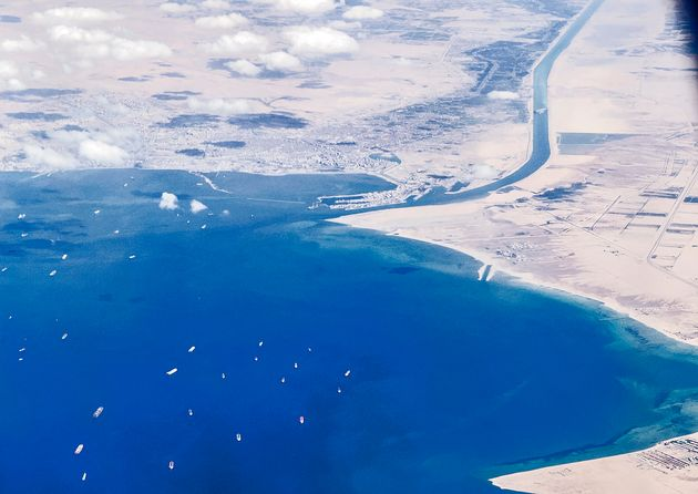 An aerial view taken on March 27, 2021 from the porthole of a commercial plane shows stranded ships waiting...