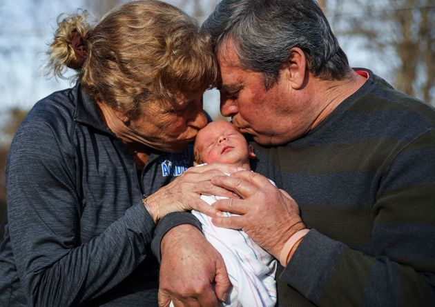CONCORD - MARCH 25: 65-year-old Kenny Banzhoff, left, and 57-year-old Barbara Higgins kiss their newborn...